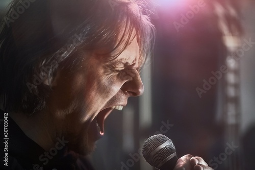 Metal singer yelling into the microphone with mouth wide open and eyes closed Canvas Print