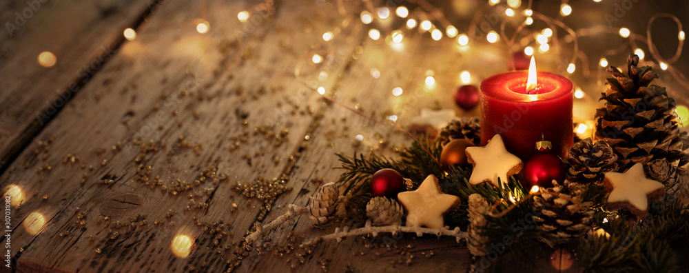 Christmas background - Red Advent candle with natural Xmas decoration, branches and pine cones on rustic wood with magic lights