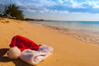 canvas print picture - A tropical Christmas image. Santa's hat lies on a sun drenched beach in the Caribbean while he thaws out in the warmth.