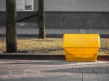 A Yellow Plastic Salt Or Sand Box On The Street.