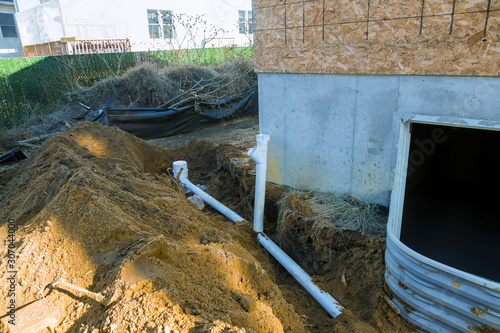 Fotografie, Obraz Plastic piping and a rainpipe against and around the a drainpipe in ground house