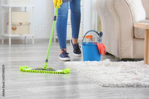 Obraz na plátně Female janitor mopping floor in room