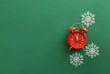Alarm Clock With Snowflakes On Color Background