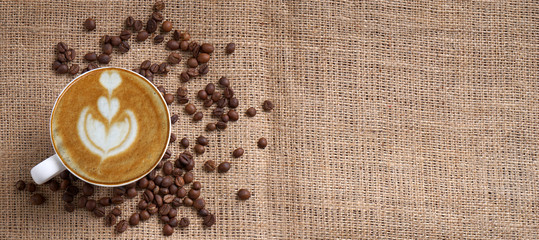 cup of coffee latte and coffee beans on jute panoramic with space for text