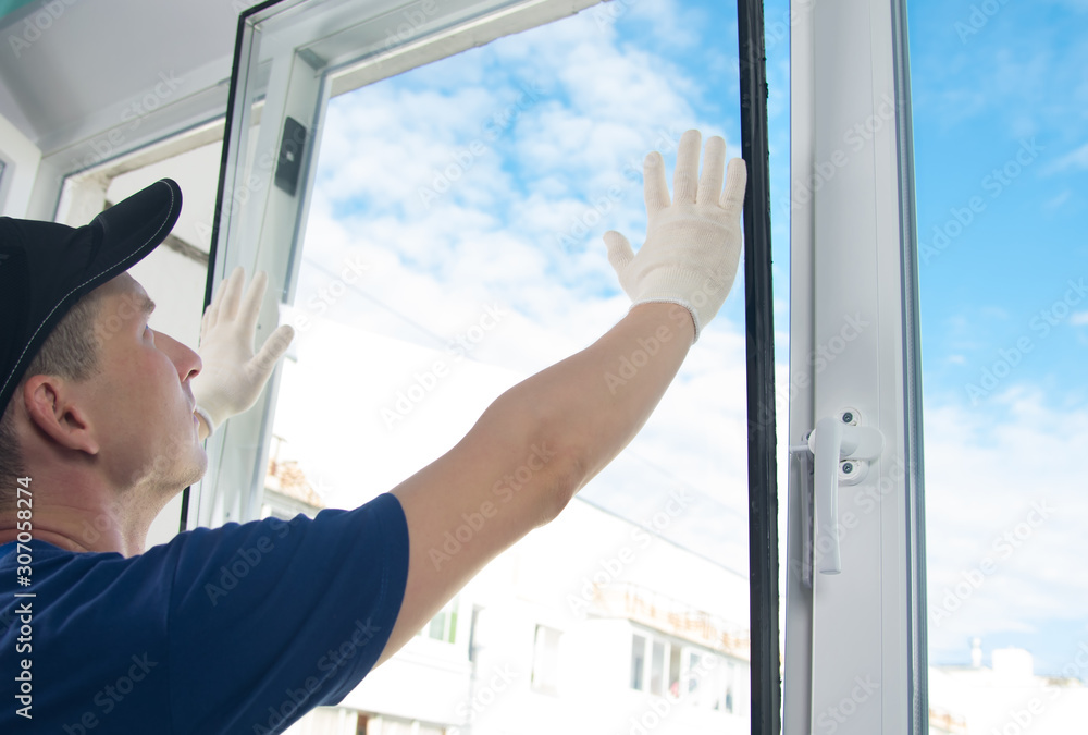 Fototapeta master in protective gloves, changing a double-glazed window in a plastic window, side view, against the blue sky