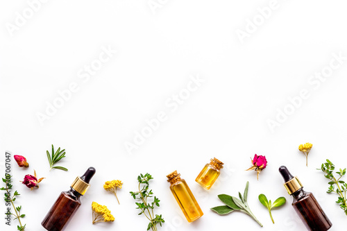 Fototapeta Natural wellness. Essential oils near herbs and leaves on white background top view pattern frame copy space obraz