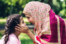 Portrait Of Happy Lovely Family Arabic Muslim Mother And Little Muslim Girls Child With Hijab Dress Smiling And Having Fun Hugging And Kissing Together In Summer Park