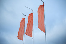 Three Red Flags In The Blue Sky Flutter In The Wind