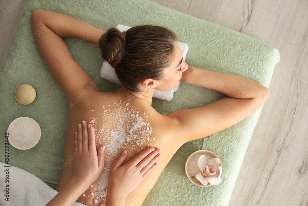 Fototapeta Young woman having body scrubbing procedure with sea salt in spa salon, top view