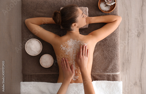 Obraz Young woman having body scrubbing procedure with sea salt in spa salon, top view - fototapety do salonu