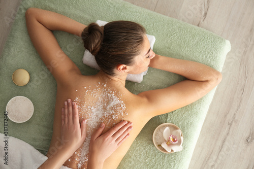 fototapeta na szkło Young woman having body scrubbing procedure with sea salt in spa salon, top view
