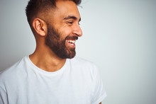 Young Indian Man Wearing T-shirt Standing Over Isolated White Background Looking Away To Side With Smile On Face, Natural Expression. Laughing Confident.