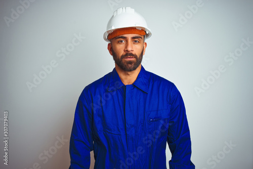Obraz Handsome indian worker man wearing uniform and helmet over isolated white background Relaxed with serious expression on face. Simple and natural looking at the camera. - fototapety do salonu