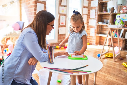 Fototapeta Caucasian girl kid playing and learning at playschool with female teacher. Mother and daughter at playroom around toys drawing on magnetic blackboard obraz na płótnie