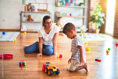 obraz dibond Beautiful teacher and toddler boy playing with tractor and cars at kindergarten
