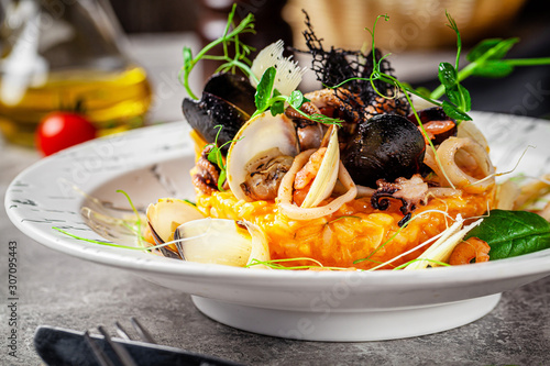 Fototapeta Italian food concept. Risotto with seafood, mussels, octopuses, squid. Serving dishes in a white plate. Modern serving in a restaurant. Background image. Copy space. obraz