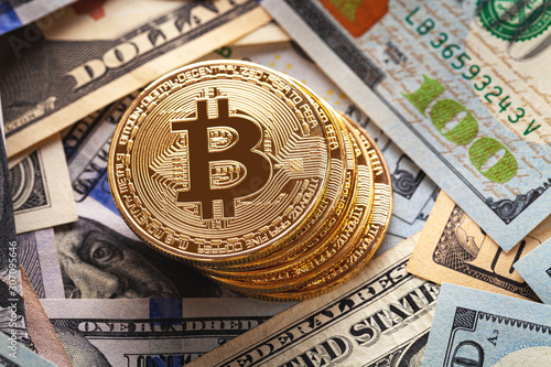 Fototapeta golden bitcoin coin on us dollars close up. Electronic crypto currency obraz