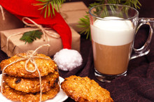 Closeup Of Christmas Crispy Oatmeal Cookies, Transparent Mug Of Coffee With Milk Or Cappuccino, Gift Boxes Wrapped In Kraft Paper, Hat Forgotten By Santa Claus On A Brown Background. Holidays Concept