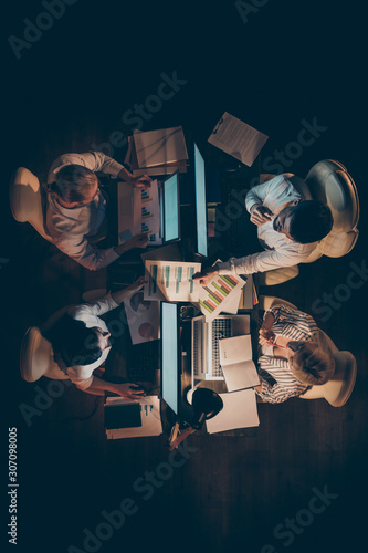 High angle above view vertical photo of hard-working four business people working overtime night looking charts schemes brainstorming lamp light dark office indoors Wall mural