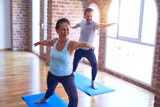 Middle age beautiful sporty couple smiling happy. Standing with smile on face practicing yoga doing warrior pose at gym