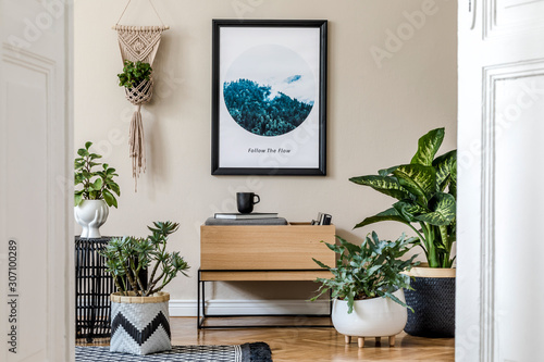 Obraz Modern scandinavian living room interior with black mock up poster frame, design commode, a lot of plants in different pots, macrame and elegant accessories. Template. Stylish home decor.  - fototapety do salonu