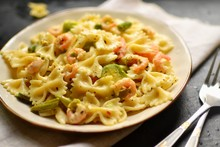 Italian Pasta In A Creamy Sauce With Shrimp On A Plate, Top View. Pasta In The Form Of Bows On A Dark Table Background.