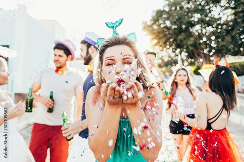 Obraz Brazilian Carnival. Young woman in costume enjoying the carnival party blowing confetti - fototapety do salonu