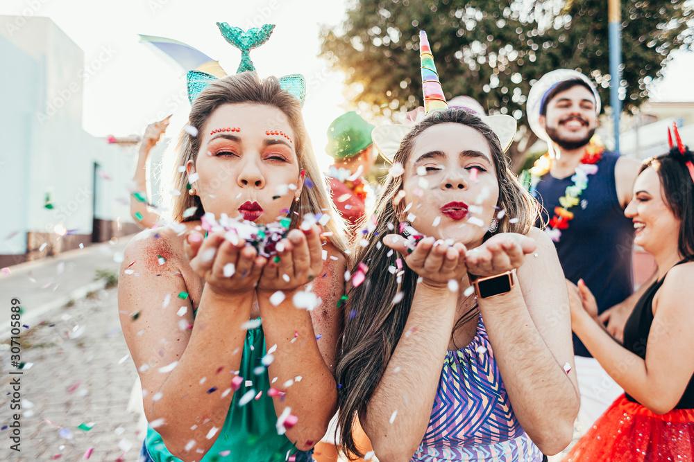 Fototapeta Brazilian Carnival. Young women in costume enjoying the carnival party blowing confetti