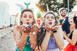 canvas print picture - Brazilian Carnival. Young women in costume enjoying the carnival party blowing confetti