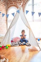 Beautiful Toddler Sitting On The Floor Inside Tipi Applauding And Smiling At Kindergarten