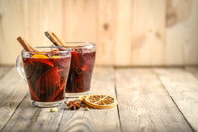 Mulled Wine In Glasses With Apples, Orange, Cinnamon And Star Anise. Hot Christmas Drink On A Rustic Background With Copy Space.