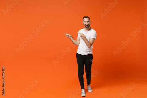 Obraz Smiling young man in casual white t-shirt posing isolated on bright orange wall background studio portrait. People sincere emotions lifestyle concept. Mock up copy space. Pointing index fingers aside. - fototapety do salonu