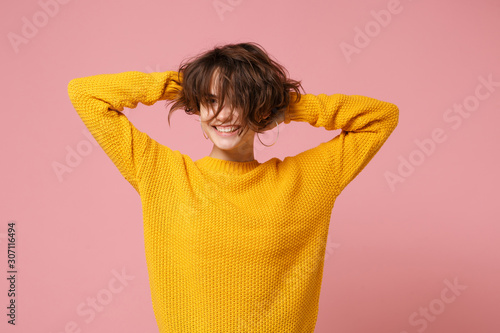 Valokuva  Smiling young brunette woman girl in yellow sweater posing isolated on pastel pink background in studio