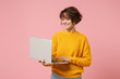 Smiling young brunette woman girl in yellow sweater posing isolated on pastel pink background studio portrait. People lifestyle concept. Mock up copy space. Holding and working on laptop pc computer.