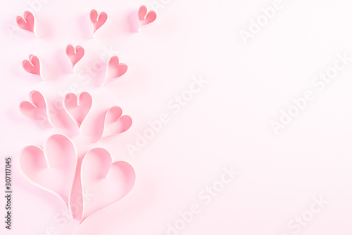 Pink paper hearts on Light pink pastel paper background. Love and Valentine's day concept.