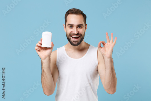 Bearded young man 20s years old in white shirt hold using antiperspirant isolated on blue pastel wall background, studio portrait Wallpaper Mural