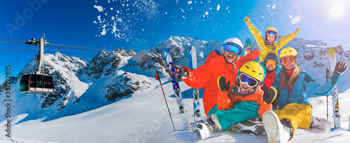 obraz PCV Happy family enjoying winter vacations in mountains . Ski, Sun, Snow and fun.