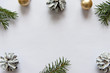 Christmas, decoration on a white table background with a blank white sheet. New Year's pine cones and golden Christmas balls. Place for text.
