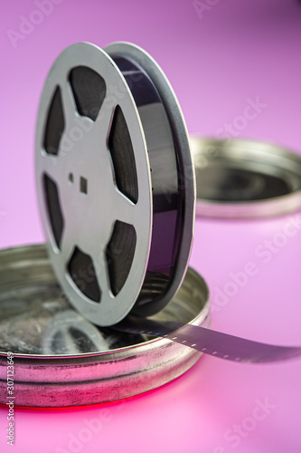 Photo old 16mm film in an aluminum bobbin and a metal box are on a pink background