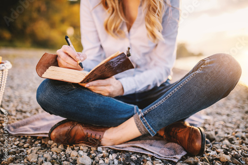 Fotografía Cropped picture of focused fashionable beautiful caucasian woman sitting near river and holding notebook