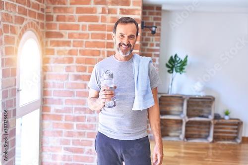 Middle age handsome sportman holding bottle of water and towel standing at gym w Billede på lærred
