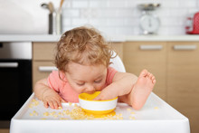 Baby In High Chair Eating Past...
