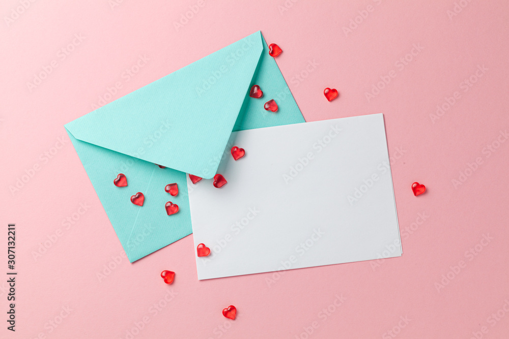 Fototapeta Love letter with red hearts. Blank template with place for text on postcard. Green envelope on pink background. mock-up