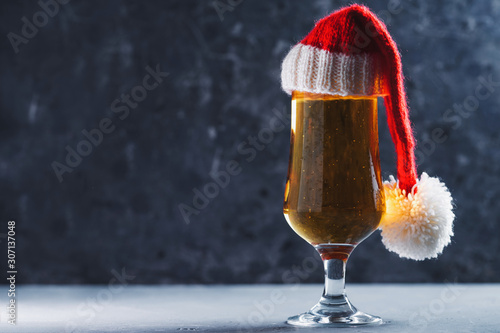 Valokuva Christmas light beer lager beer in glass with Santa hat on dark background copy
