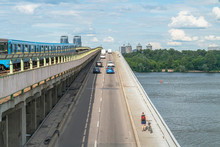 Metro Bridge In Kyiv, Ukraine Across The Dnieper River In Summer Time With Various Types Of Transport, From Most Ecological To Environment Polluting.