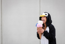 Beautiful, Young Woman In Penguin Costume Is Eating Deco Ice Cream In Front Of Concrete Wall