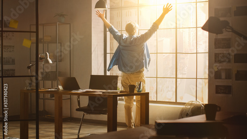 Fotografie, Tablou Creative Developer Looks out of His Office Window, Happily Celebrates Project Breakthrough by throwing Hands in the Air
