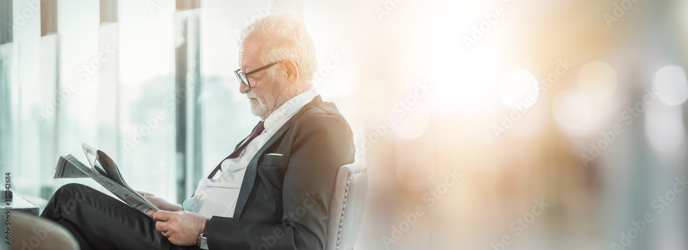 Fototapeta Senior man business professional in suit sitting in lounge of hotel. Man modern executive successful , lifestyle business handsome portrait. Success concept