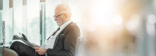 Obraz Senior man business professional in suit sitting in lounge of hotel. Man modern executive successful , lifestyle business handsome portrait. Success concept - fototapety do salonu