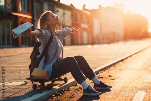 obraz dibond Smiling girl sitting on long board in the city during sunset with arms outstretched.
